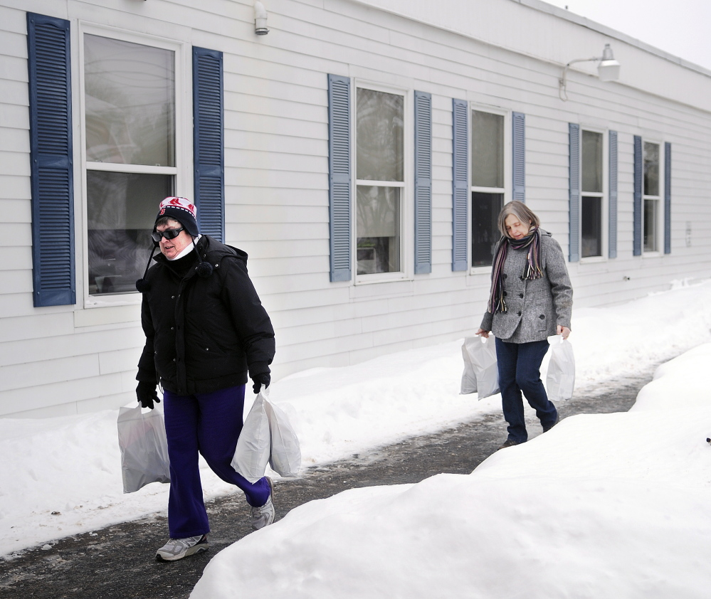 Connie LaFlamme, right, and her sister-in-law, Debbie LaFlamme, carry bags of groceries into the Hamlin School in Randolph on Thursday. The volunteers deliver groceries through Food for Thought to provide supplemental nutrition to students in the Gardiner area school district.