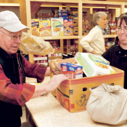 Volunteer Bob Veilleux helps slide a box of food for Anne Robinson on the first day of operation for the new Fairfield Interfaith Food Pantry on Thursday. In the background volunteer Louise O'Brien waits to assist another client.
