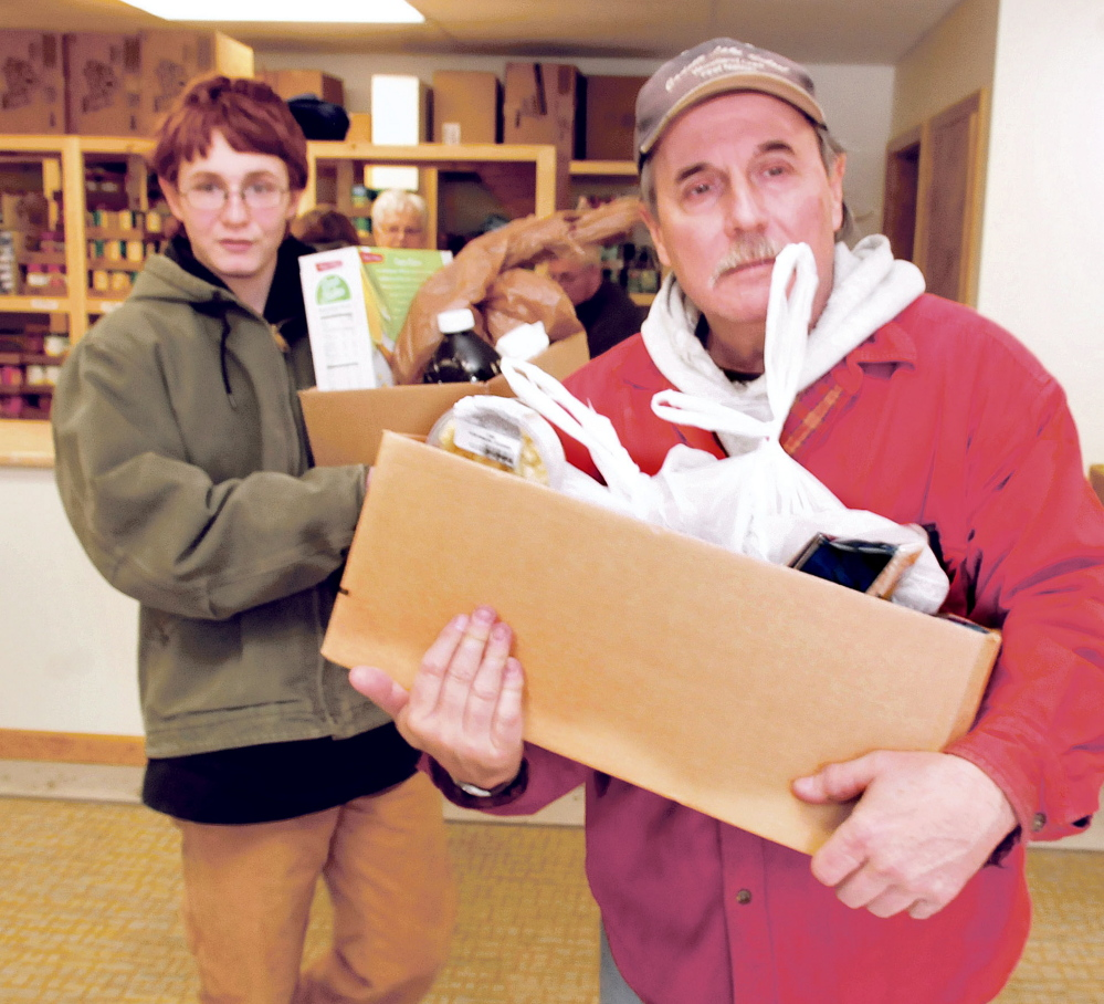 Volunteers Cameron Patterson, left, and Paul Cairnie carry out boxes of food for recipients on the first day at the new Fairfield Interfaith Food Pantry on Thursday.