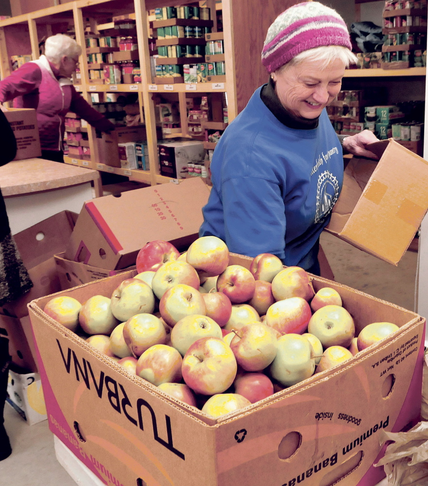 Volunteer Kathy Keup fills fruit requests at the new Fairfield Interfaith Food Pantry on Thursday.