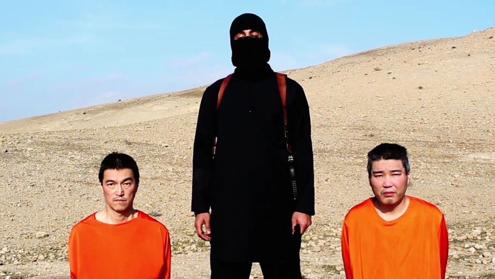 """This image taken from an online video released by the Islamic State shows the group threatening two Japanese hostages who were later killed. One of the men posing with hostages in the videos, nicknamed """"Jihadi John,"""" has been identified as a man known to the British intelligence services since at least 2009."""