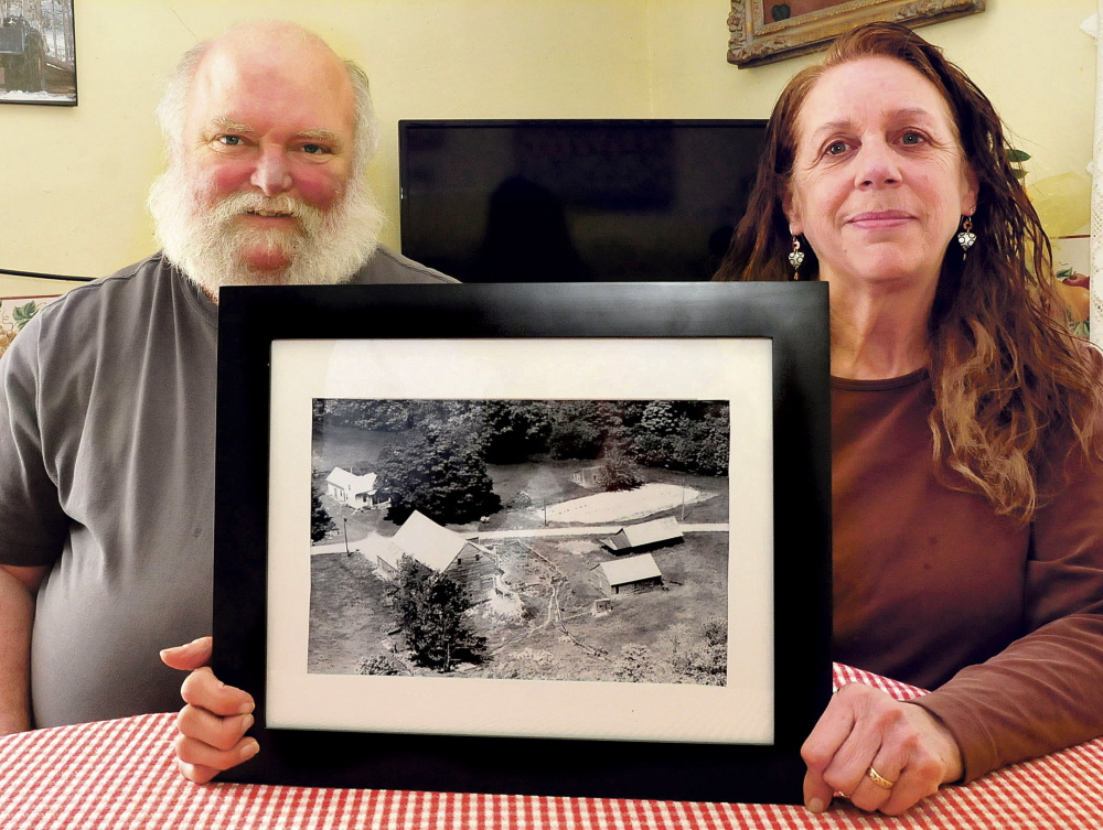 Rene and Janet Burdet hold a copy of an aerial photograph of their farm in Cornville taken in 1963. Their home is at upper left but most outbuildings have succumbed to age.