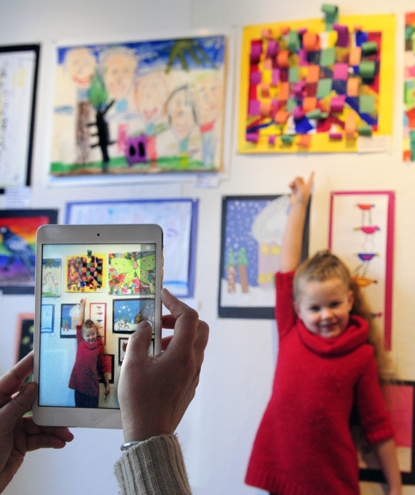 Mount Vernon Elementary School kindergartner Kyleigh Pinkham poses for a photo with her work Saturday at the opening of the Young at Art Show at the Harlow Gallery in Hallowell.