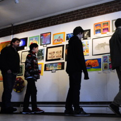 Showgoers inspect the 200 works on display at the opening of the Young at Art Show on Saturday at the Harlow Gallery in Hallowell.