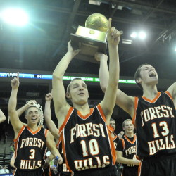 Forest Hills High School's Brandon Ouellette, 10, center and Matt Turner, 13, raise the trophy after defeating Fort Fairfield High School 51-45 in the Class D state championship game Saturday at the Cross Insurance Center in Bangor.