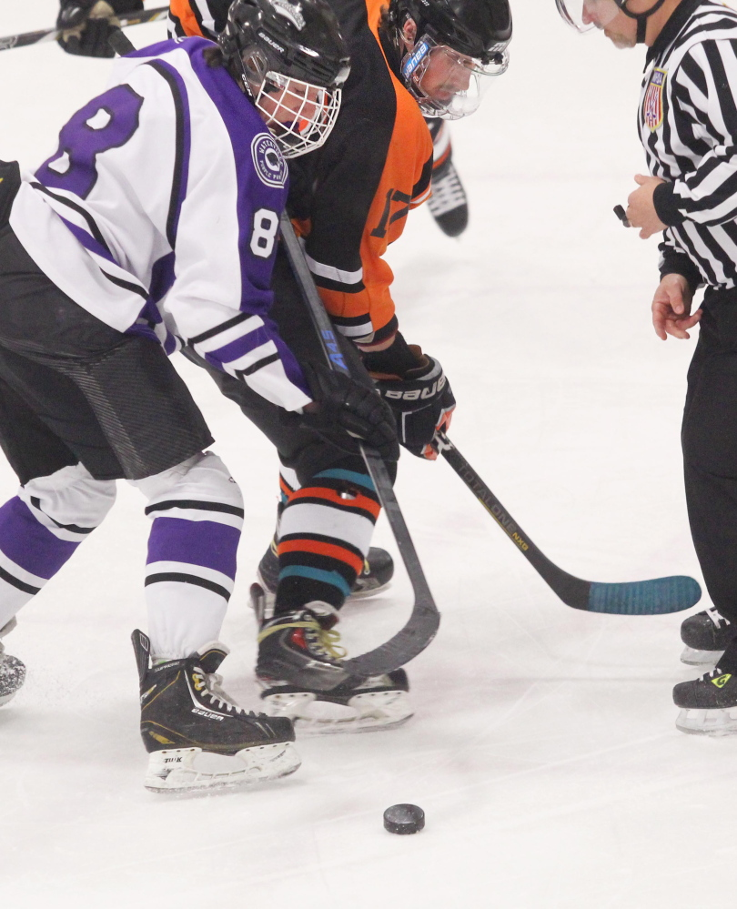 Waterville Senior High School's Justin Wentworth and Winslow High School's Alex Berard battle for control of a faceoff during first-period action at an Eastern Class B semifinal at Sukee Arena in Winslow on Saturday night.