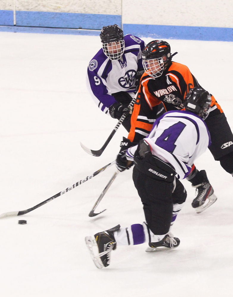 Winslow High School's Jacob Trask skates the puck between Waterville Senior High School's Dalton Henderson, 9, and Michael Oliveira, 4, during first-period action at an Eastern Class B semifinal playoff game at Sukee Arena in Winslow on Saturday night.