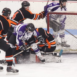 Waterville Senior High School's Michael Oliveira collides with Winslow High School goalie Andrew Beals at the Black Raiders net minder covers the puck during first-period action at a Eastern Class B semifinal playoff game Saturday at Sukee Arena in Winslow.