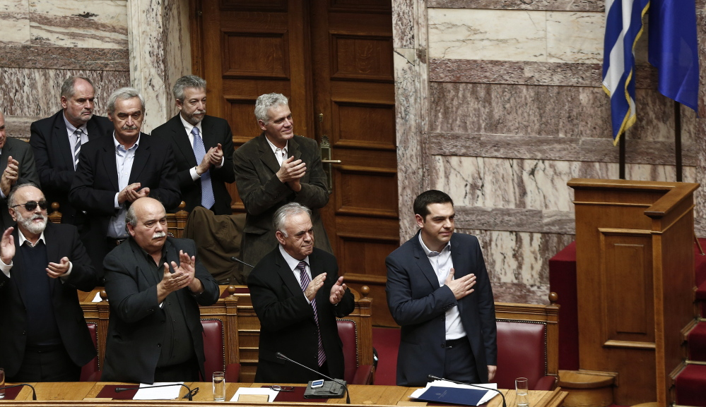 Greek Prime Minister Alexis Tsipras, right, acknowledges applause by members of his government Sunday following his first major speech in parliament in Athens