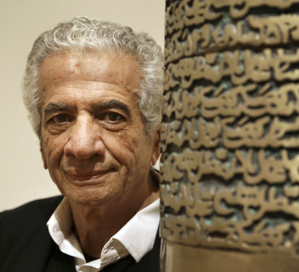 """Iranian artist Parviz Tanavoli stands near a detail of his sculpture, """"Poet Turning Into Heech."""" Heech means """"nothing"""" in Persian."""