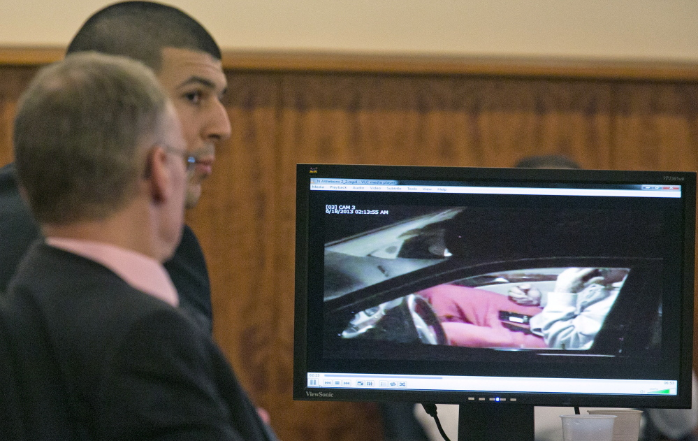Aaron Hernandez, rear, and his attorney Charles Rankin watch surveillance video of Hernandez handling cell phones during his murder trial in Fall River, Mass., Tuesday.