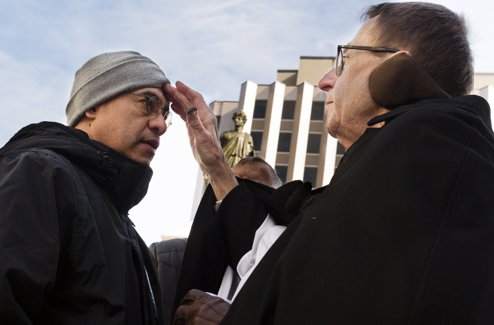 Ezequiel Rubio, left, receives the mark of ashes from the Rev. Richard Rasner in Portland's Monument Square on Ash Wednesday. Rasner, an Episcopal priest at the Cathedral Church of St. Luke, was joined by the Rev. Ben Shambaugh and the Rev. Larry Weeks as they offered Christians in downtown Portland an opportunity to celebrate the start of the Lenten period preceding Easter, which falls on April 5.