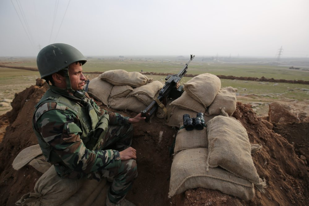 A Kurdish soldier stands guard, on the road between Mosul and Tal Afar in Iraq. Three Peshmerga brigades will be part of the effort to recapture Mosul from Islamic State militants.
