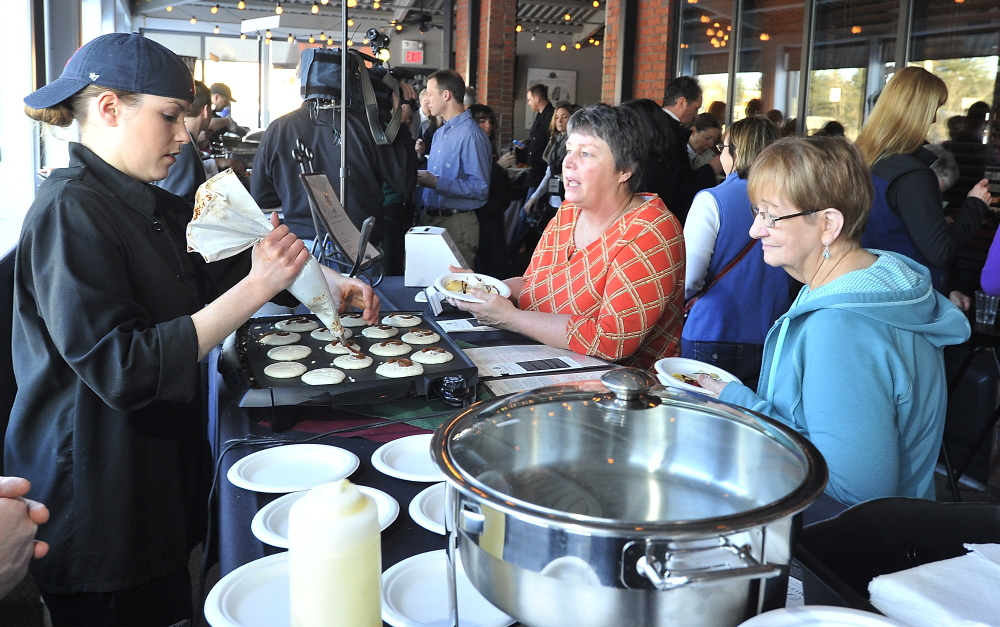 SOUTH PORTLAND, ME - FEBRUARY 27: Mary Gresik of Scarborough, center, and Phyllis Sargent of OOB await their serving of a cinnamon bun pancake with cream cheese frosting from head chef Nicole Steinmark, left, of Bintliff's American Cafe at the Incredible Breakfast Cook-Off held at Sea Dog Brewing Company in South Portland. (Photo by Gordon Chibroski/Staff Photographer)