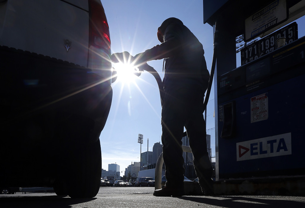 Sonu Singh pumps gas for a motorist at a gas station in downtown Newark, N.J., where the cash price for regular unleaded was listed at $1.71 on  Jan. 23. The Associated Press
