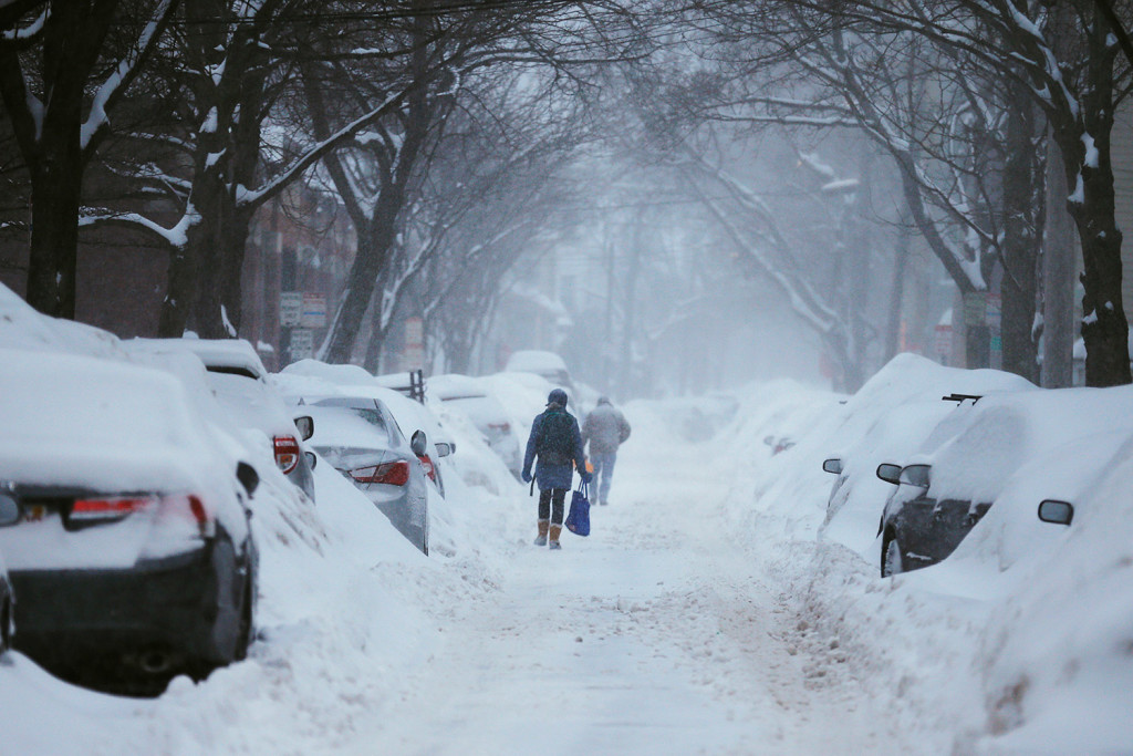 Pedestrians make their way along a snow-covered street during a Feb. 9 , 2015 winter storm in Cambridge, Mass.