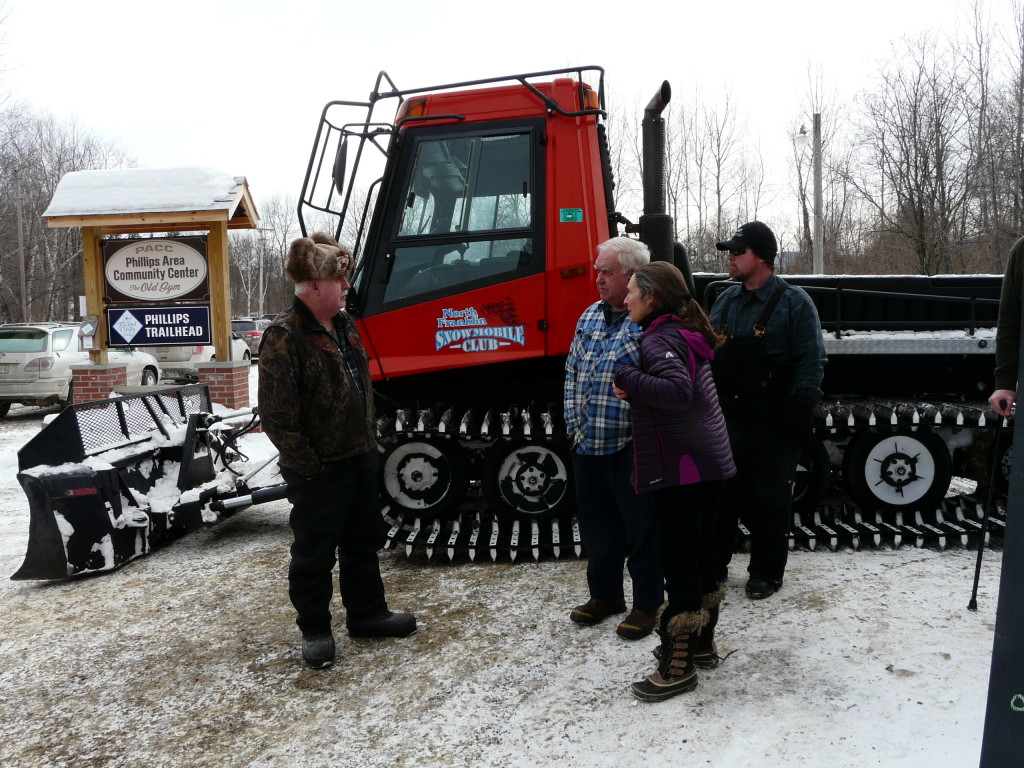 From left, the North Franklin Snowmobile Club's groomer Dennis Presby, High Peaks Alliance volunteers Betsy Squibb and Douglas Marble, and George Berry gather on Saturday at the Phillips Area Community Center in Phillips to celebrate the Orbeton Stream Project conservation easement, completed in December.