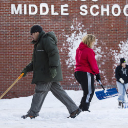 Saco Middle School custodians Lodel Seneres, Joi MacDonald and Donna Jose, clear snow from Saturday's snow fall, on Sunday. Carl D. Walsh/Staff Photographer