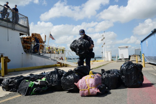 A Coast Guardsman helps offload approximately 1,100 pounds of cocaine in San Juan, Puerto Rico, on Tuesday. The contraband and three Dominican smugglers captured by the Coast Guard Cutter Tahoma were transferred to the Drug Enforcement Administration. U.S. Coast Guard photo