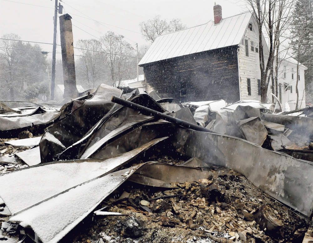 The home of Rick and Tina Belanger lies in blackened ruins in front of the Caratunk post office on Nov. 17, the day after a fire destroyed the home, another nearby home, garage and did serious damage to the post office.
