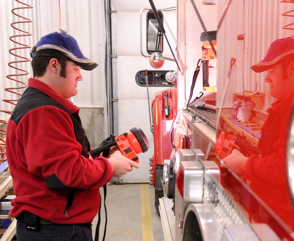 Chesterville Fire Lt. Joseph Hastings checks that one of the flashlights work while he and other firefighters checked over two of the department trucks on Tuesday at the fire station in Chesterville. Hastings, 19, is also a member of the Farmington Fire Department. Central Maine departments are feeling the crunch of fewer volunteers, less money and more required training.
