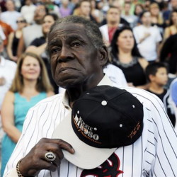 Former Negro Leaguer and Chicago White Sox player Minnie Minoso stands during the national anthem before a baseball game between the Chicago White Sox and the Texas Rangers in Chicago in April 2013.