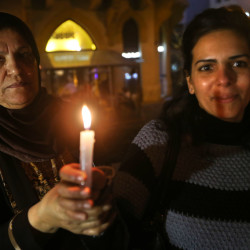 Palestinian women hold candles during a vigil held by a Palestinian group in solidarity with Christians abducted in Syria and Iraq, in downtown Beirut, Lebanon Sunday.