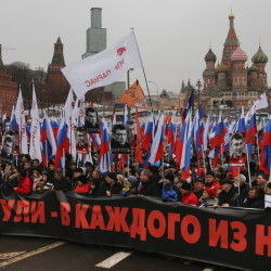 "A large crowd in central Moscow, fronted by a banner reading ""those bullets for everyone of us,"" march together as a protest of the death of liberal opposition leader Boris Nemtsov who was gunned down on Friday near the Kremlin."