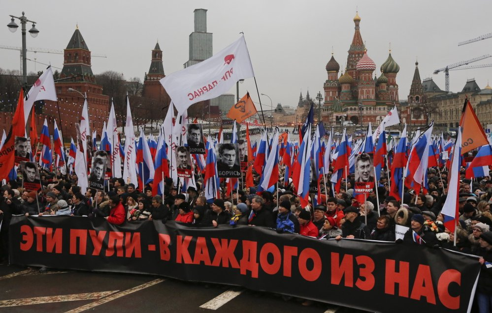 """A large crowd in central Moscow, fronted by a banner reading """"those bullets for everyone of us,"""" march together as a protest of the death of liberal opposition leader Boris Nemtsov who was gunned down on Friday near the Kremlin."""