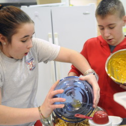 Sarah Cook-Wheeler and Devin Young mix macaroni and cheese after class at Cony High School in Augusta. The students are learning how to prepare healthy meals as part of the Food Matters program.