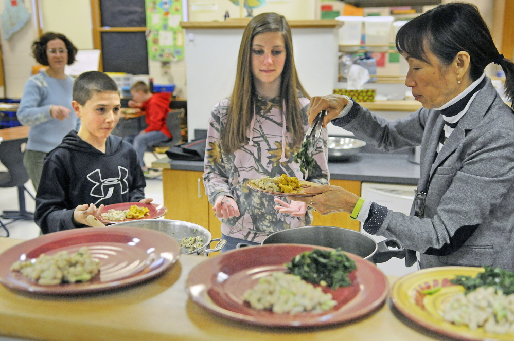 Alyssa Wingate, right, serves a meal she volunteered to help Cony High students Liz Young and Benjamin Lucarelli prepare after classes at the Augusta school. The students learn how to make healthy meals as part of the Food Matters program.