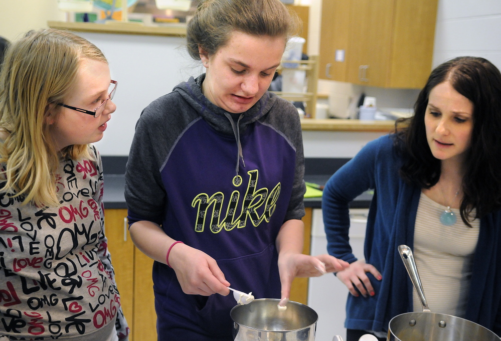 Dietitian Jacqueline Stevens, right, helps Cony High students Megan Greaton, center, and Camryn Elliott measure several tablespoons of butter while cooking a meal after classes at the Augusta school. Stevens is teaching the students how to prepare healthy meals as part of the Food Matters program.