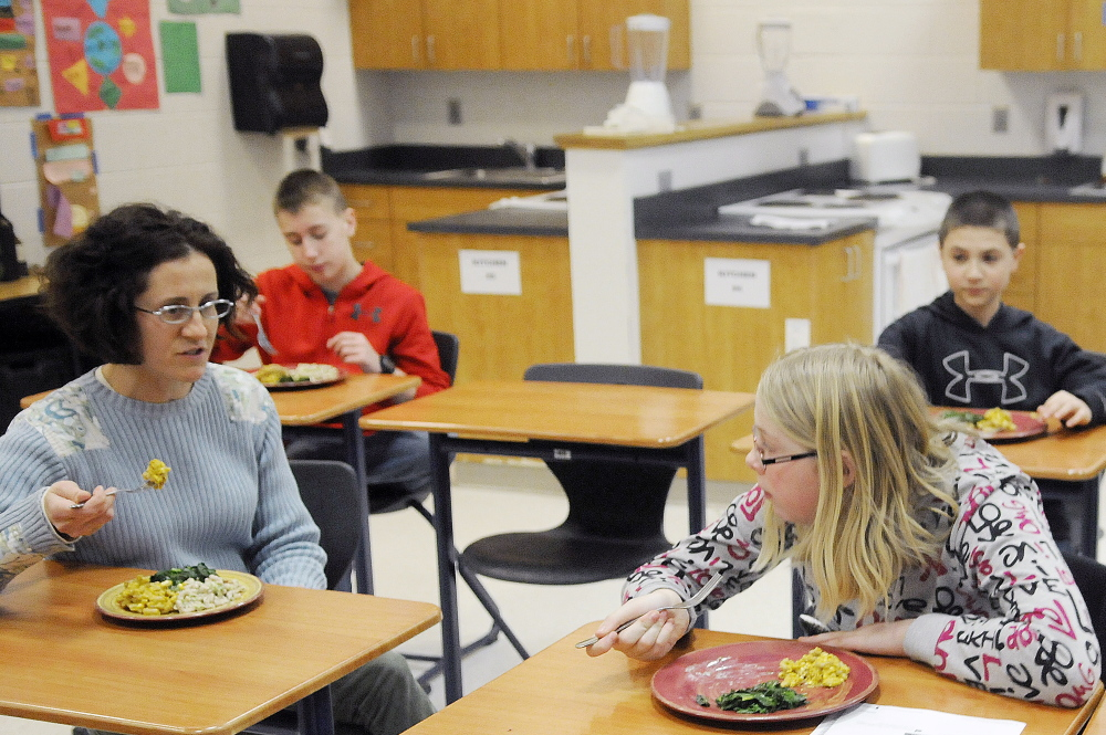 Cony High School teacher Brenda Weis, left, shares a meal her students prepared in the Food Matters program after classes at the Augusta school.