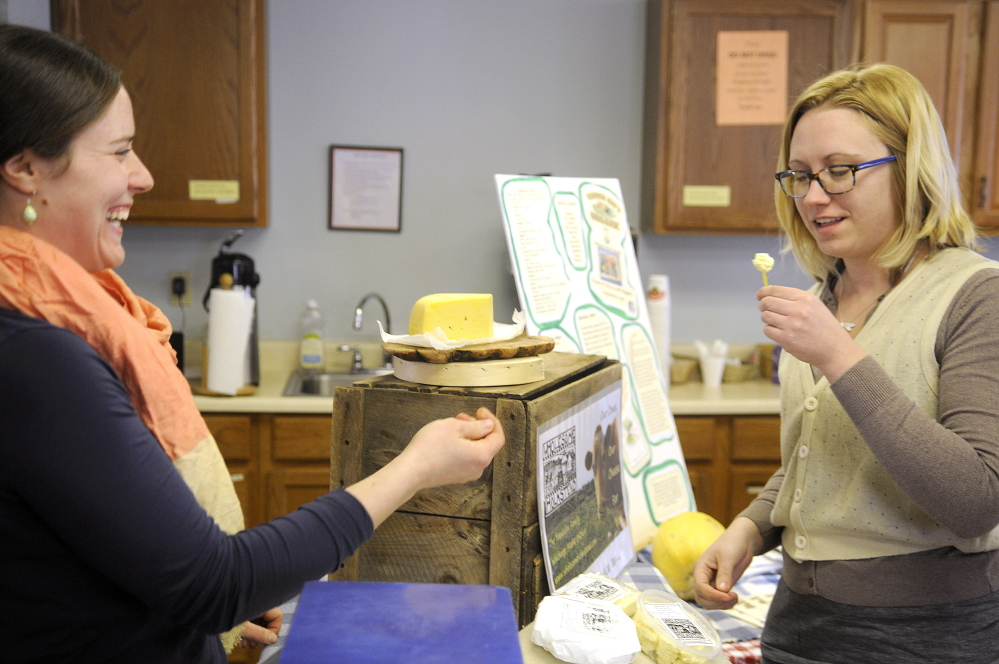Kate Harris, right, samples Guernsey cheese kurd from Anne Trenholm's farm, Wholesome Holmstead of Winthrop, during a community supported agriculture exhibition in Hallowell on Sunday. Customers had an opportunity to meet a variety of local farmers at the event. Wholesome Holmstead raises Angus beef cattle and milk-fed pork in addition to dairy products such as cheese.