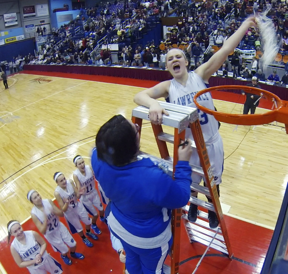 Lawrence manager Kellie Goldsmith, left, and center Nia Irving celebrate on top of the ladder after cutting down a net after the Bullodogs beat Thornton Academy for the Class A state championship Saturday at the Augusta Civic Center.