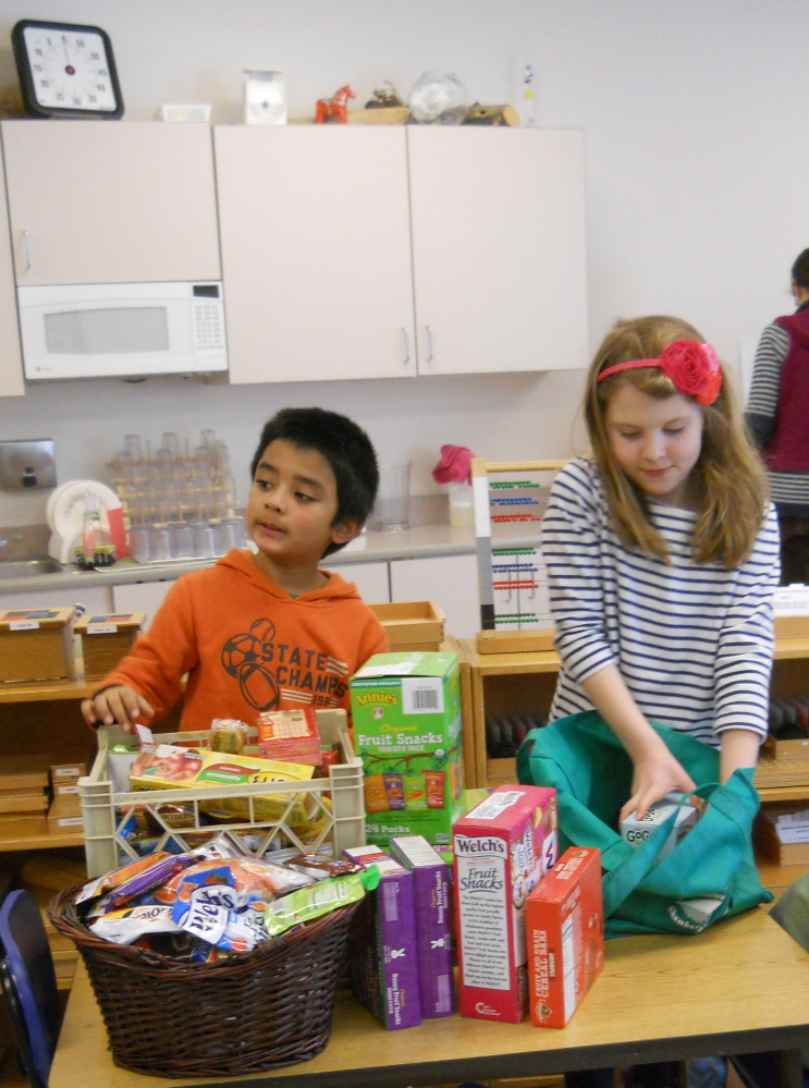 Share Your Snack Week was held recently at the Kennebec Montessori School in Fairfield. Students were invited to bring in an extra snack to share with children at the Mid-Maine Homeless Shelter. From left, are elementary students Savya Acharya and Kate Rice as they organize the donations for delivery.