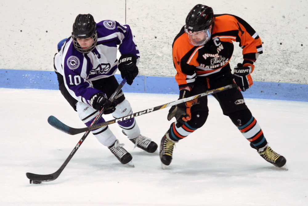 Waterville Senior High School's Matthew Jolicoeur and Winslow High School's Alex Berard battle for the puck during first-period action at a Eastern Maine Class B semifinal last week at Sukee Arena in Winslow. The Black Raiders will play Messalonskee on Tuesday night at the Alfond Arena in Orono for the regional championship. The winner of that game moves on to the Class B state championship game Saturday at the Androscoggin Bank Colisee in Lewiston. The last time Winslow won the Class B title was in 2008.