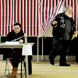 Norridgewock resident Elwin Shields steps out of a voting booth past ballot clerk Lexia Dorr during elections at the Mill Stream School before the annual Town Meeting on Monday. Dorr said that it has been unusually quiet for elections this year. Following the election, residents met to tackle a 45-article warrant that included the town budget, an ordinance to require building permits on all building alterations and a proposal for a new fire station.