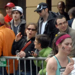 Dzhokhar Tsarnaev, second from left, and Tamerlan Tsarnaev, center, stand in the crowd as Boston Marathon runners headed to the finish line on Boylston Street in Boston on April 15, 2013.