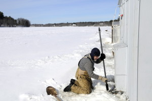 George Shaw, of Pittston, jacks his smelt camp off the Kennebec River in Pittston on Tuesday. As the river ice has built up, the persistence of freezing temperatures has kept the base of the camp below the ice surface all winter, he said. With a thaw inevitable, Shaw elevated the camp off the ice to be able to pull it ashore quickly. He estimates that more than 2 feet of ice remain on the river.