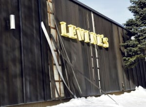 Detached aluminum siding leans against the former Levine's clothing store Tuesday in Waterville. The city's code enforcement officer says that while the siding is not heavy, it could pose a traffic hazard if it blows into the busy intersection of Front, Main and Bridge streets.