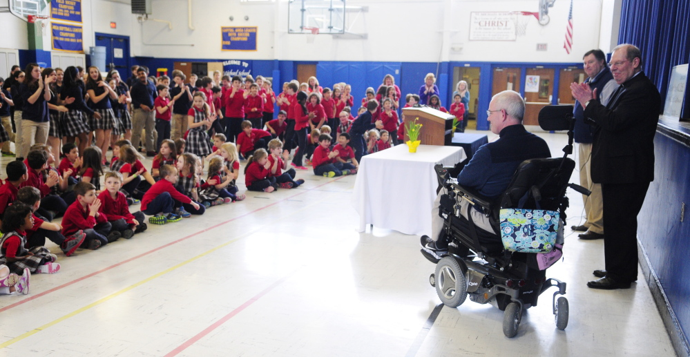 Augusta Police Chief Robert Gregoire receives a standing ovation Wednesday from students in the St. Michael School gymnasium in Augusta.