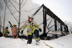 Monmouth Fire Chief Dan Roy steps through two feet of snow Wednesday after helping haul a hose to firefighters battling a blaze that destroyed a garage full of industrial equipment on Route 197 in Litchfield.
