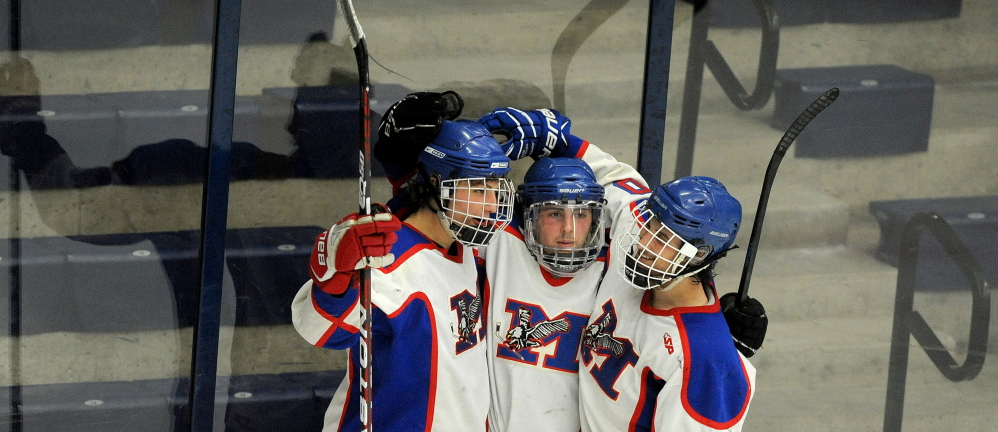 Messalonskee High School's Jake Dexter (7) celebrates with teammates Jared Cunningham (19), center and Brandon Nale (10) right after scoring on Winslow High School goalie Andrew Beals (35) last week. The Eagles play Gorham on Saturday for the Class B championship.