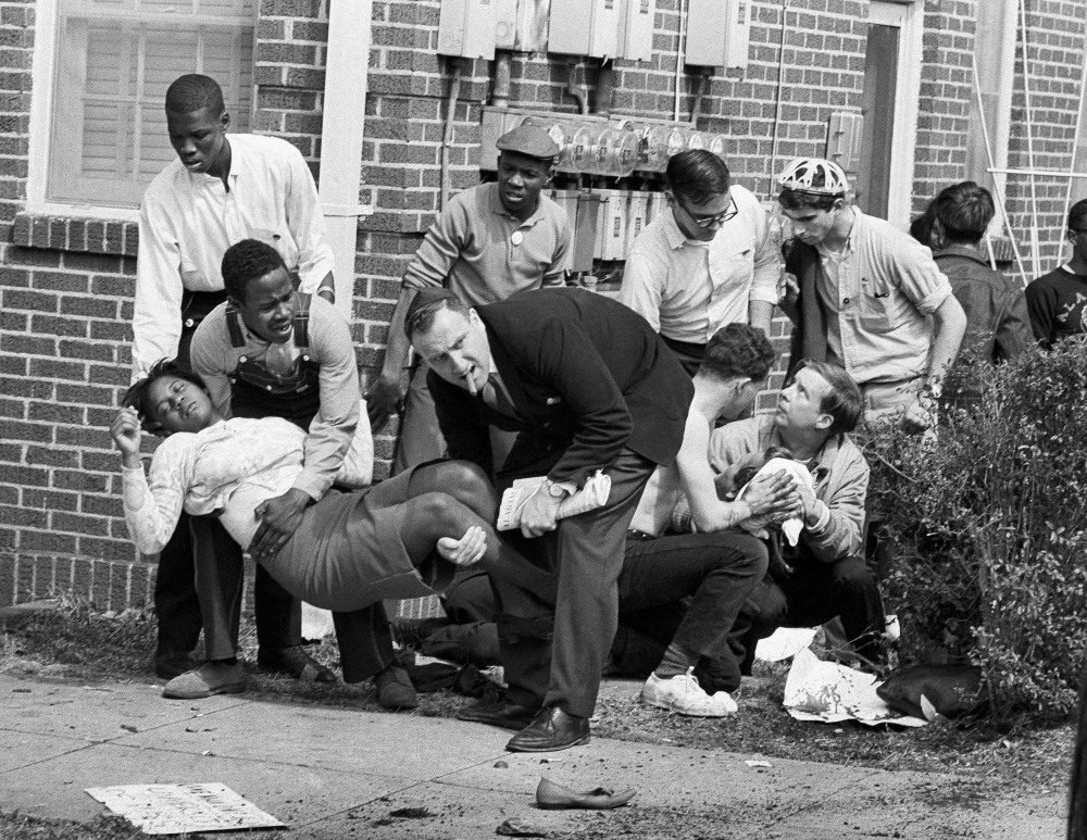 """In this March 7, 1965, photo, Amelia Boynton is carried and another injured man tended to after they were injured when state police broke up a demonstration march in Selma, Ala. Boynton, wife of a real estate and insurance man, has been a leader in civil rights efforts. The day, which became known as """"Bloody Sunday,"""" is widely credited for galvanizing the nation's leaders and ultimately yielded passage of the Voting Rights Act of 1965."""