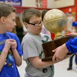 Lawrence High School junior Nia Irving, 16, hands off the Gold Ball to Albion Elementary School fifth-grader Gavin Cummings, 11, as third-grader, Leuka Dunham, 8, left, watches during a visit from the Lawrence girls basketball team Friday at Albion Elementary School. The state champs brought the Gold Ball to area schools for the day.