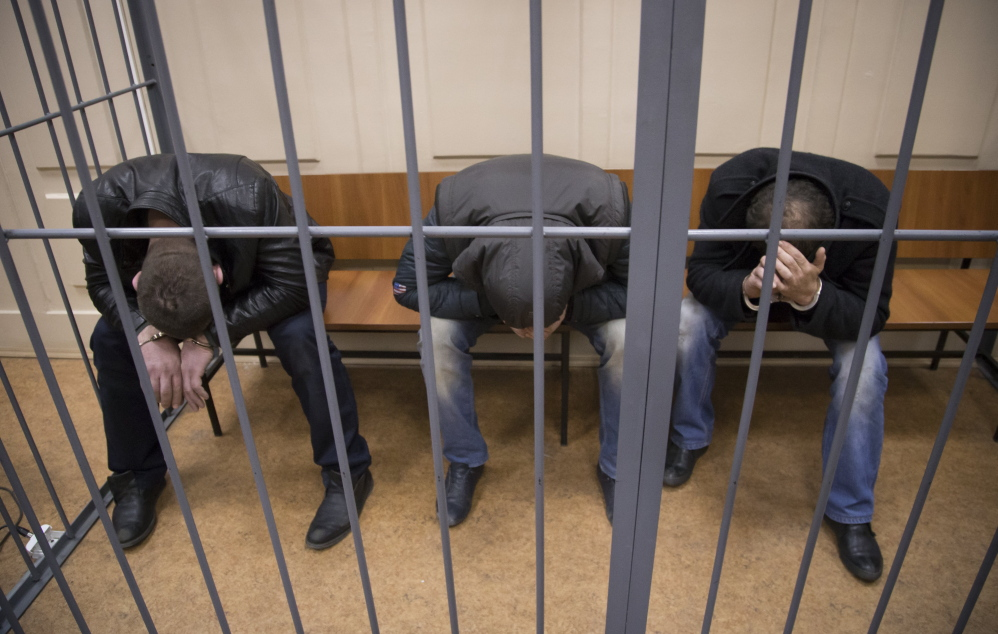 Three of the men suspected of involvement in the killing of Russian opposition leader Boris Nemtsov – from left, Tamerlan Eskerkhanov, Shagid Gubashev and Khamzad Bakhaev – sit Sunday in a Moscow courtroom. They were ordered held in jail.until a decision is made on whether to charge them.