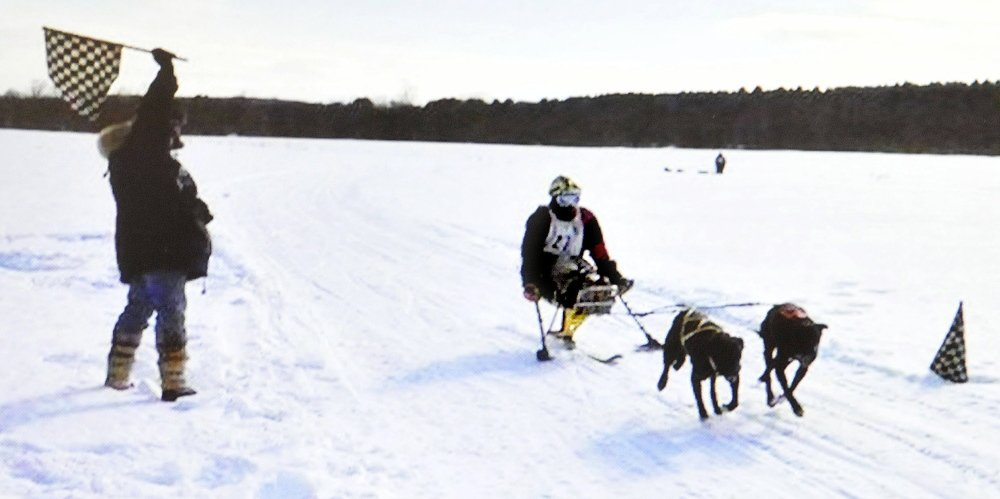 Joe Albee, of Vassalboro, crosses the finish line while skijoring with dogs in a race in Alaska. Albee passed his friend in background.