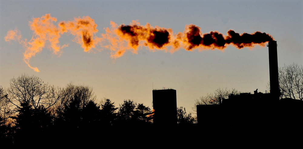 The setting sun fills the blowing smoke with color coming from the Sappi paper mill in Skowhegan in November 2014.