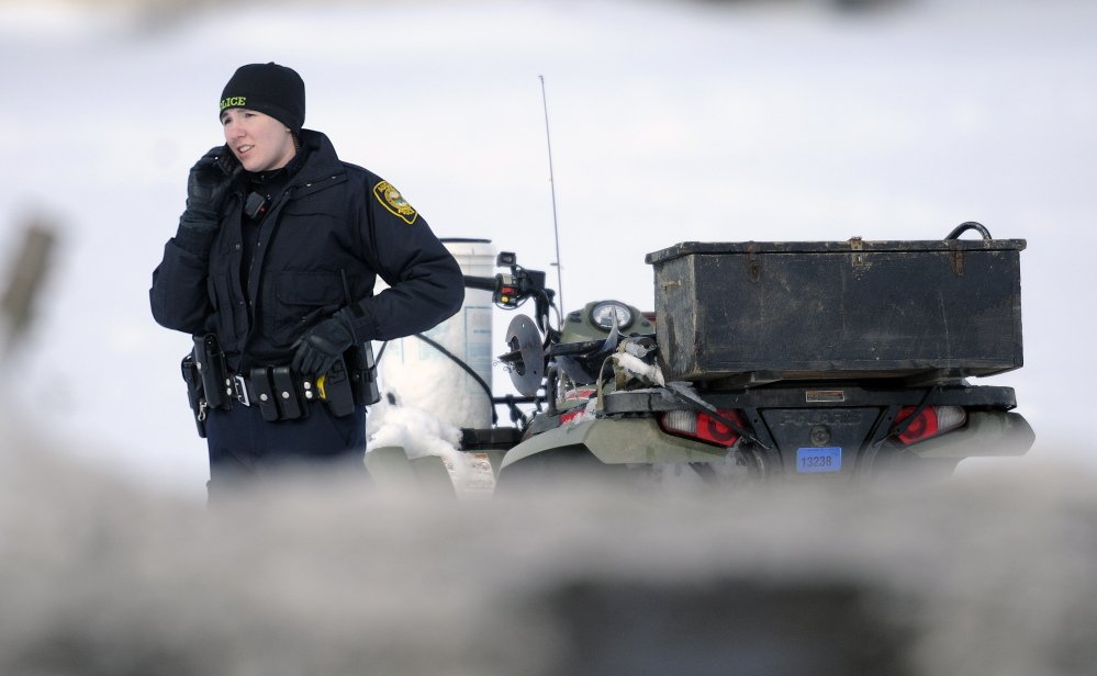 Augusta Police Officer Laura Drouin stands next to an all-terrain vehicle on Togus Pond. The body of the man who was operating the ATV was found on the pond about a hundred yards from Route 105 in Augusta.